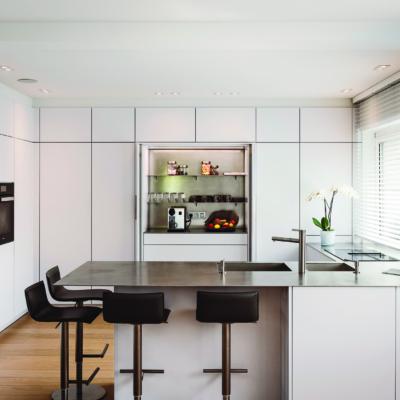 Helle Küche mit vielen Schränken und Barhockern