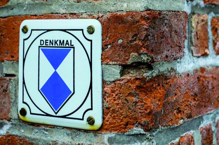 Denkmalschutz-Plakette auf rotem Mauerwerk