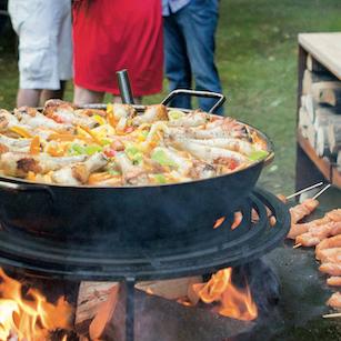 Grilltopf mit Essen im offenem Feuer geschwenkt