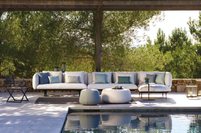 Helle Lounge-Möbel vor Poolpanorama