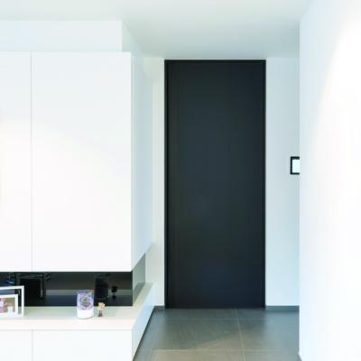 Dunkle Tür vor weißen Wänden