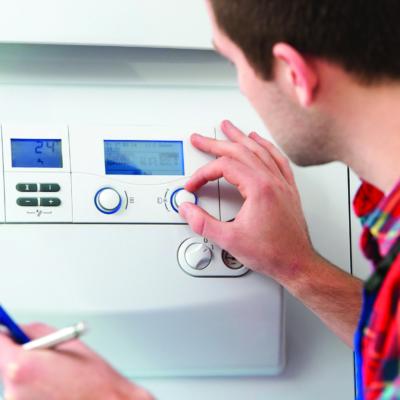 Person reguliert Temperatur am Thermostat